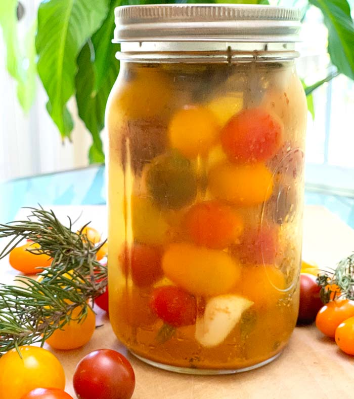 Rosemary pickled cherry tomatoes. The tomatoes are skewered on rosemary cuttings.