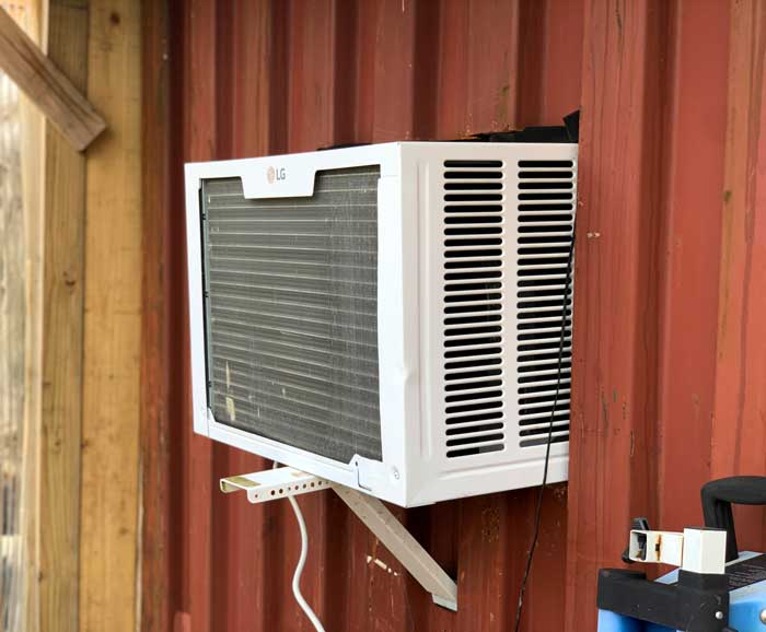 A wall AC unit helps convert an old shipping container into an on-site refrigeration system.