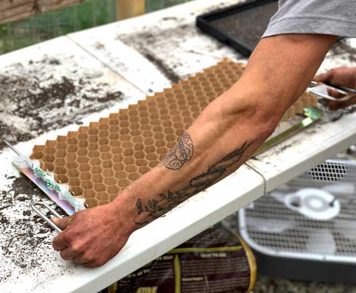 Chris setting up a Paper Pot transplanter seed flat/cells.